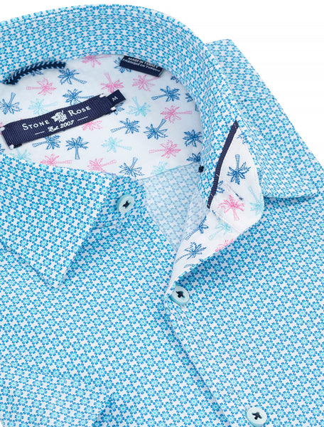 Close-up view of the label, contrasting palm tree print, and buttons on a Stone Rose short-sleeve button-up.