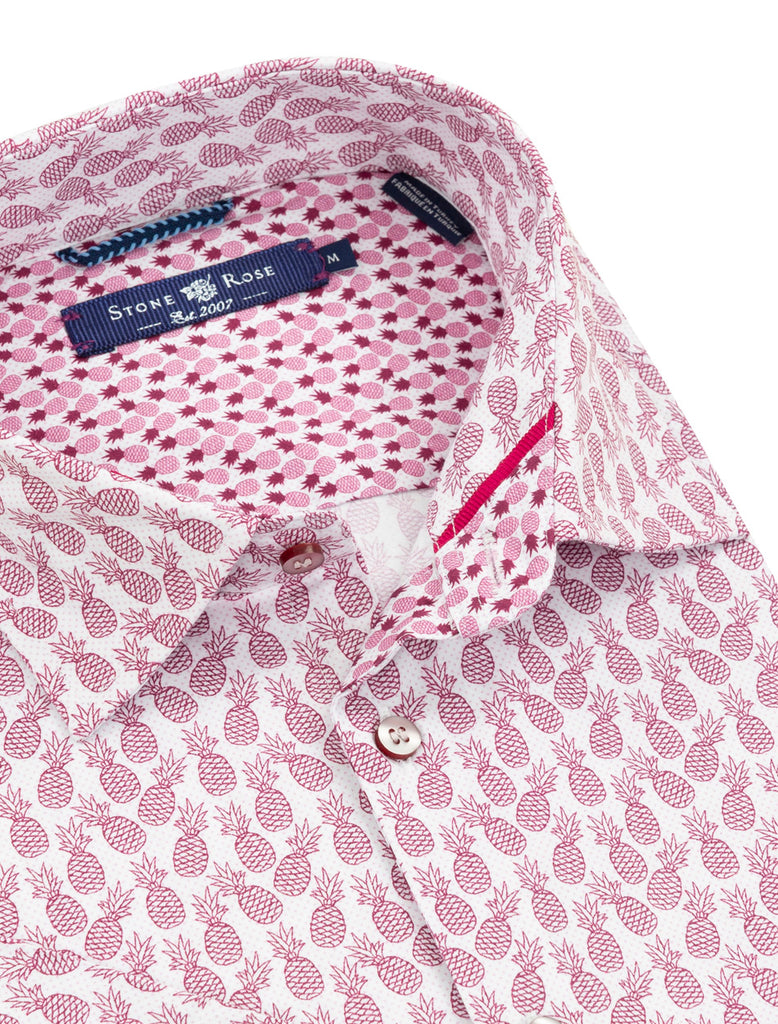 Close-up image of a short-sleeve button-up from Stone Rose with a pink pineapple print.