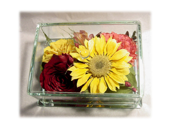 Within this 5x5 glass box design, you will be able to showcase one focal flower and have it come to life with surrounding filler flowers and added greenery, leaving you with a one of a kind work of art. Although space is limited within this glass box, you do have the option to add a small, cherished token to remember a special day or to honor a loved one. (Size 5x5 box available) Prices start at $150.