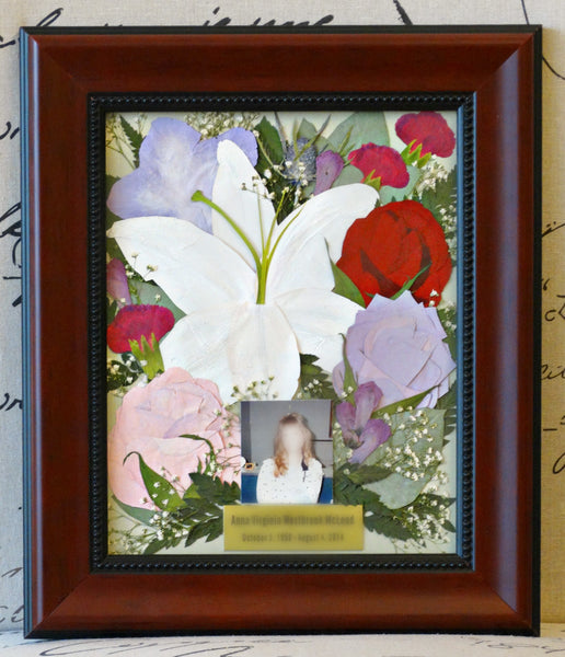 In this beautiful 8x10 frame, a free form Victorian inspired design fills the frame and allows you to showcase an assortment of memorial flowers as a work of art. With an option to include a custom nameplate, a small prayer card and/or photograph. With a large selection of frames and mats, you can complete your design. Prices start at $295.