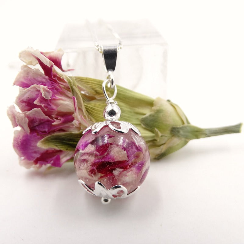Pink flowers petals inside a memorial necklace