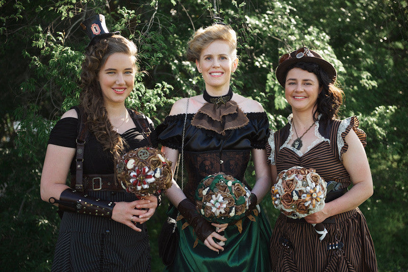 Bridesmaids outfitted by Gallery Serpentine and holding steampunk bouquets
