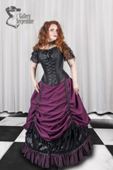 front view of a red headed model wearing a black steel boned over bust corset and burgundy victorian skirt with a hoop underneath it