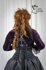 back view of the Deathly Deathly Hallows Bolero Shrug in dark purple stretch velvet with silver Deathly Deathly Hallows print worn on a model with the matching corset