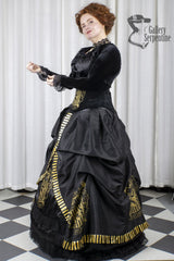 model holds the sleeve of the Hufflepuff black stretch velvet Bolero worn on top of the victorian style cosplay corset gown