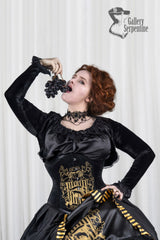 model eating grapes shows the sleeves of the Hufflepuff Bolero for the HP corset cosplay gown
