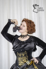 smiling red headed model eating grapes on a shoot for the Hufflepuff victorian corset gown for fantasy cosplay costumes