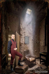 stylised decayed old building setting for the shoot of the authentic old west high waisted burgundy outlaw trousers worn with black button on suspender braces and 1800s era black victorian shirt