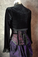 back view on a mannequin of a black stretch velvet bolero shrug designed to be worn over corsets to show off the waistline