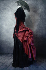 side view of the deluxe length victorian bustle skirt in garnet taffeta worn over a black satin under skirt and bustle cage