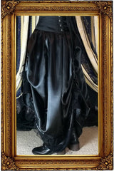on model showing the neo victorian steampunk style Seraphina skirt side on worn without a hoop skirt underneath in black satin