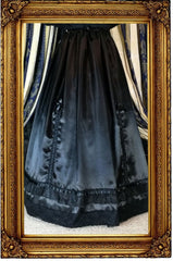 front of the new neo victorian Seraphina skirt in black satin with ribbon braid adjusters worn over a hoop skirt