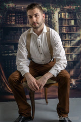 Westworld fantasy image of Westeros model wearing the Gent shirt in natural toned cotton, tan button on braces and high waisted tan outlaw pants, seated model in library