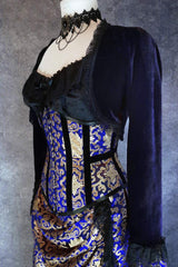 side front view showing waist compression of the royal blue and gold steel boned under bust corset worn on a mannequin with a black under corset top and dark purple velvet bolero shrug on top
