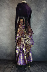 side back view showing back of purple velvet bolero on top of royal purple gold brocade victorian style bustle skirt with matching under bust corset trimmed in black velvet shown on a mannequin