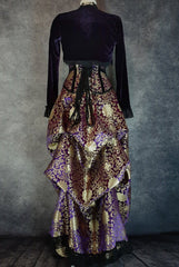 back view of royal purple gold brocade victorian style bustle skirt with matching under bust corset trimmed in black velvet shown on a mannequin