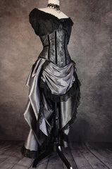 full length side front view showing the matching silver bustle skirt in the Australian made under bust tight lacing corset in a dark silver taffeta overlaid with delicate black lace and trimmed with black velvet ribbon down the corset bone channels