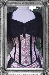 up close view of the black velvet trimmed steel boned under bust corset as part of the new pink renaissance brocade victorian under bust corset and matching Victorian Bustle Skirt on a mannequin in outdoor setting