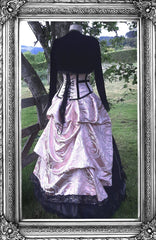 back view of the pink and black renaissance brocade gown showing the back lacing on the corset and a black velvet bolero worn over the gown