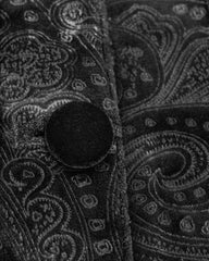 up close detail of the black velvet buttons and silky paisley jacquard on the new men's 3/4 length gothic victorian aristocrat coat with baroque lace and braid detailing made from black velvet