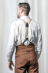 back shot of the Westworld fantasy image of Westeros model wearing the Gent shirt in natural toned cotton, tan button on braces and high waisted tan outlaw pants