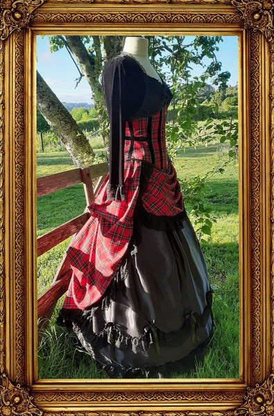 side view of the victorian punk corset ball gown in red stewart tartan fabric in an outdoor setting