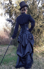 full back view of victorian woman wearing a corset over the gothic victorian black sateen lace trimmed high low bustle skirt with adjustable waist sizing made in Australia for Gallery Serpentine