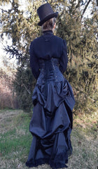 full back view showing black victorian blouse, steel boned corset and the gothic victorian black sateen lace trimmed high low bustle skirt with adjustable waist sizing made in Australia for Gallery Serpentine