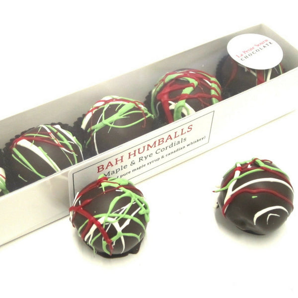 "A long box of five chocolates.  the chocolates have erratic design in traditional Christmas colours: red, green and white.  The name on the box is ""Bah Humballs: Maple Ry Cordials"""