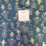 Caramel Macchito Bar sitting on sheets of gold and green robot patterned wrappers