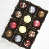 A view from above of our 12 piece box, with white chocolate, and painted chocolates in red, silver and gold.