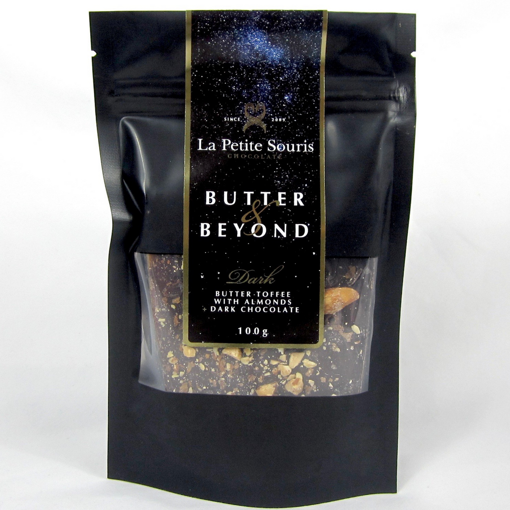 A 100g bag of butter and beyond toffee.  The bag is black with a space themed sticker showing stars.   The label has a gold outline.  The bag has a clear window which shows the product.  It looks pretty good.