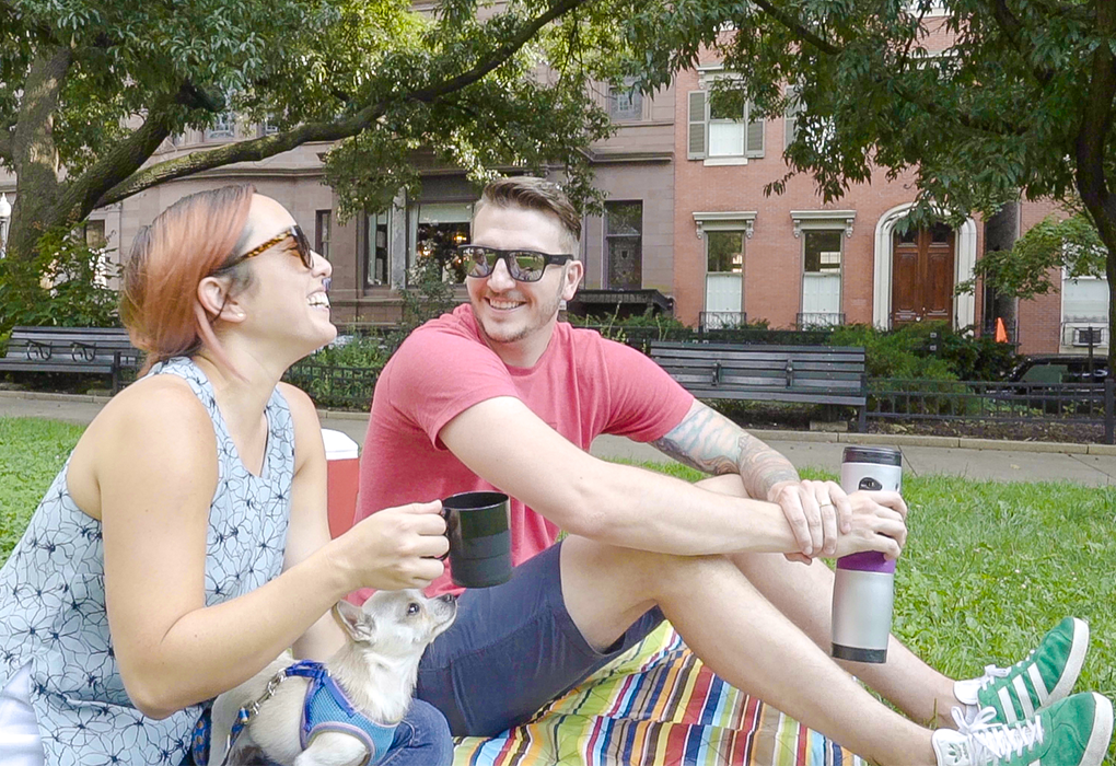Young millennial couple in park laughing and enjoying coffee from mojoe™ Portable Single Serve Coffee Maker