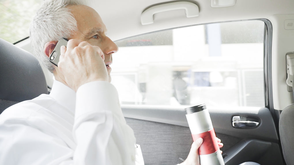 Business man in car on cell phone holding mojoe™ Portable Single Cup Coffee Machine