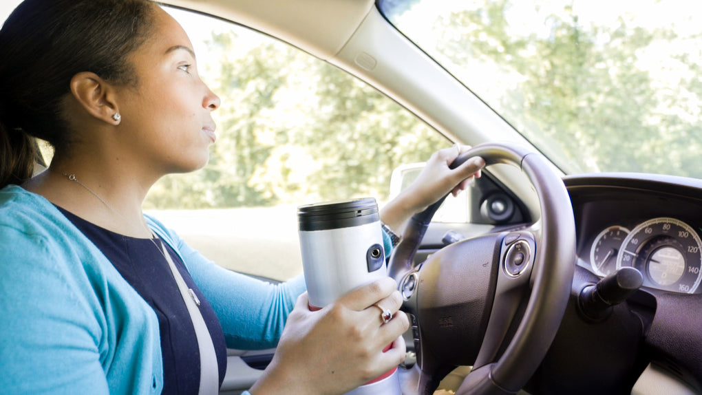 Busy woman driving car and commuting while brewing with mojoe™ Mobile In Car Coffee Maker