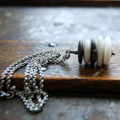 Cairn necklace made with white beach stones and black river rocks. It hangs from a stainless steel rolo chain by Wear Your Wild