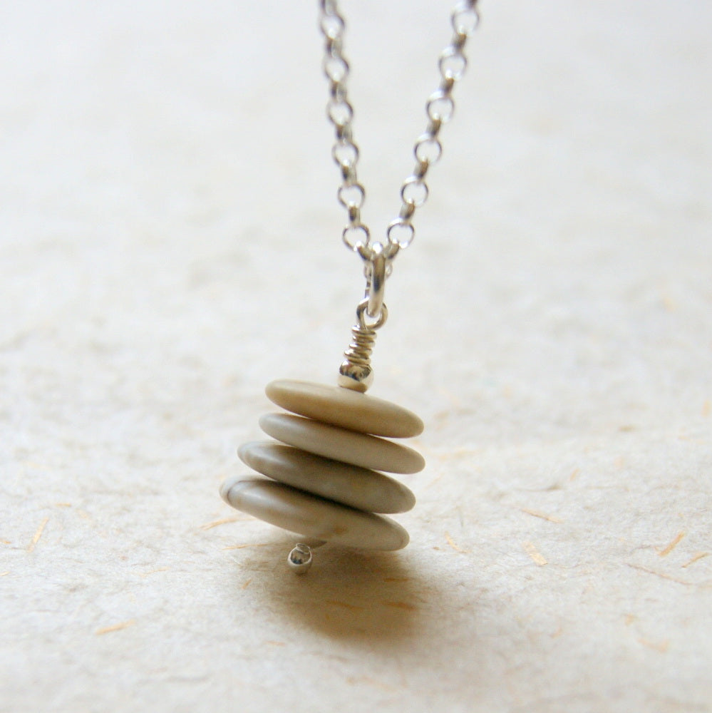 A petite beach stone Cairn necklace with four stones in shades of beige and tan hanging from a sterling silver chain.