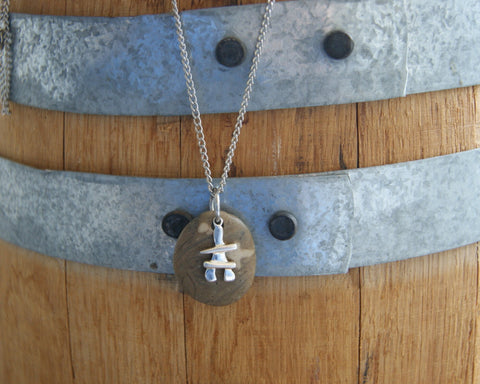 A beach stone necklace with a sterling silver Inukshuk charm by Wear Your Wild