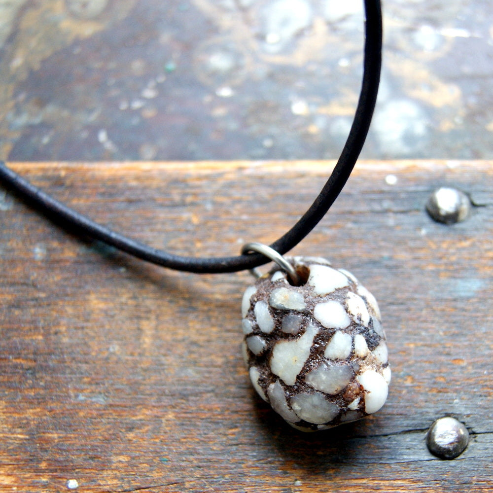 A brown and white piece of smooth, surf tumbled terrazzo hangs from a brown leather cord.