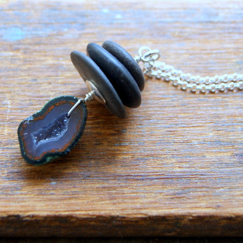 A small geode slice is combined with three black river stones to make a Cairn necklace.