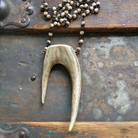 A forked deer antler tip necklace with a vintage rosary chain made with bone beads.