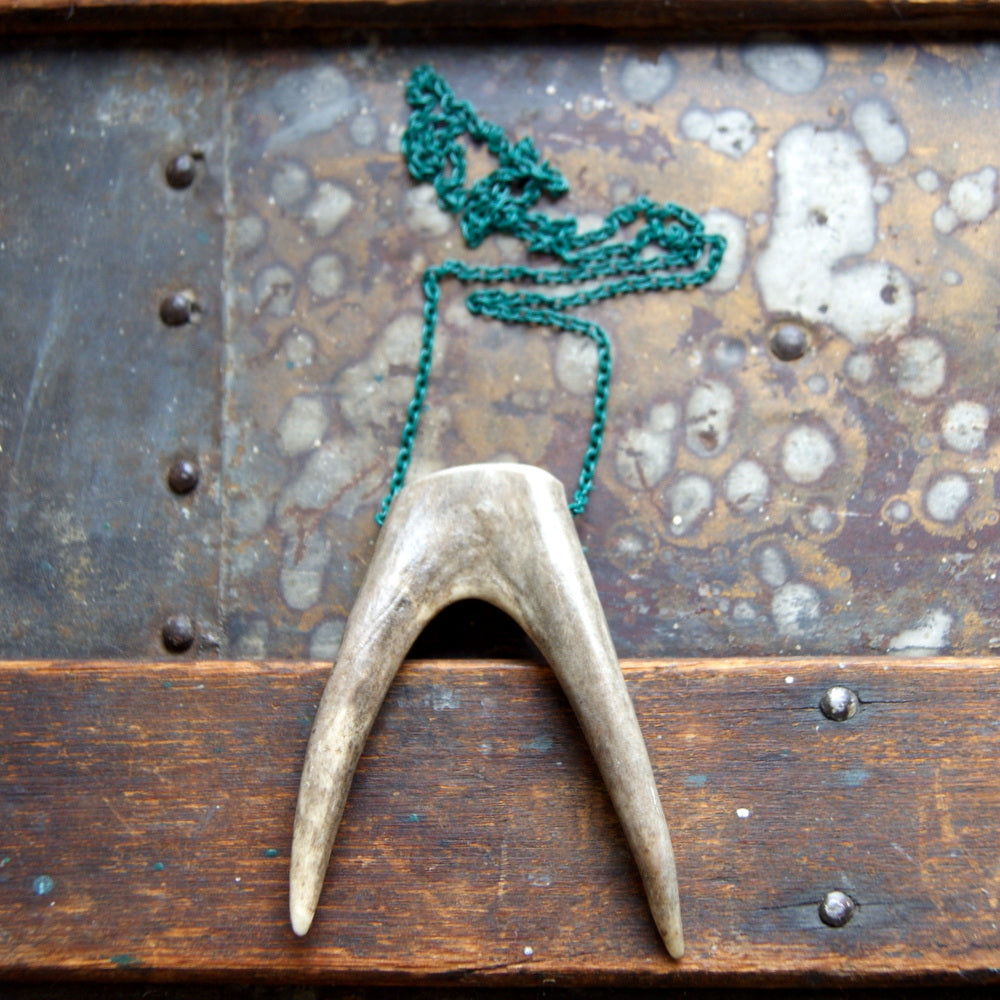 A forked antler tip necklace with a vintage green enameled chain.