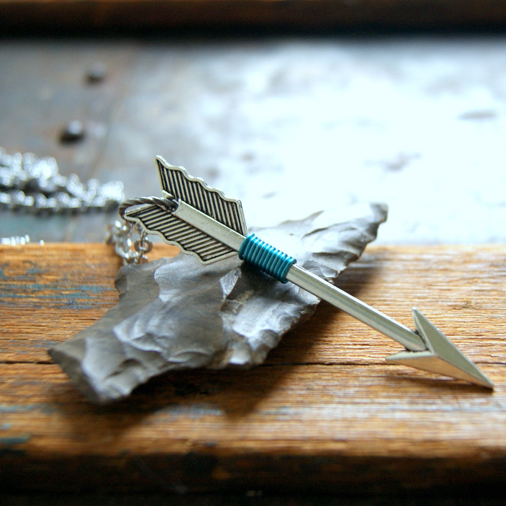 A silver arrow necklace wrapped with turquoise wire by Wear Your Wild