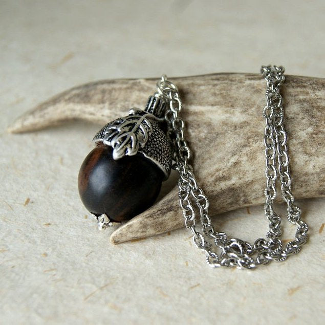 An acorn necklace made by combining a dark brown tiger ebony bead and an antiqued silver acorn bead cap by Wear Your Wild.