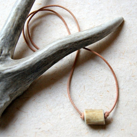 A necklace made with a deer antler bead knotted onto a natural tan Greek leather cord by Wear Your Wild.