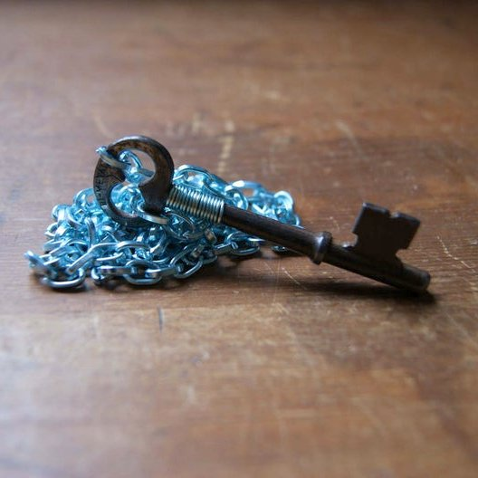 Necklace made by wrapping an antique skeleton key with aqua blue wire and hanging it from an aqua blue aluminum chain by Wear Your Wild
