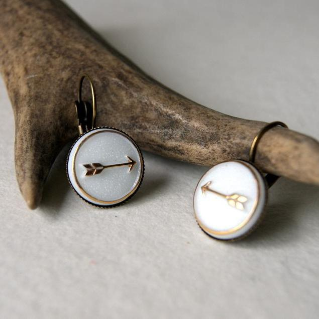 Earrings made with vintage gold and white glass arrow cabochons attached to lever back earwires.