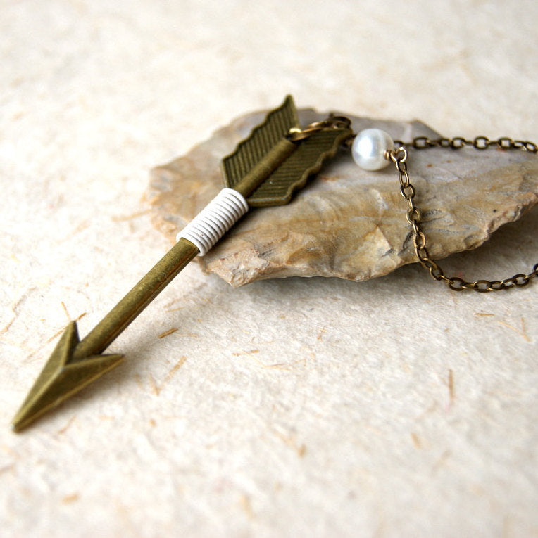 Necklace made with a bronze arrow pendant wrapped with ivory colored wire and hung from an antiqued brass chain connected together with a white pearl.