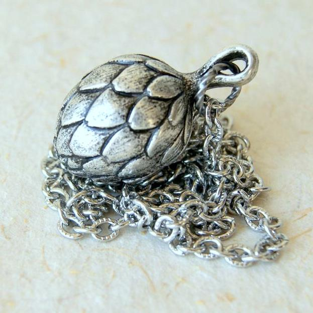 A vintage plastic artichoke pendant with a silver metal finish hanging from a stainless steel chain.