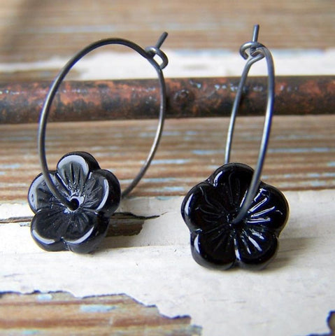 Vintage black glass flower beads are threaded onto oxidized sterling silver hoop earrings by Wear Your Wild
